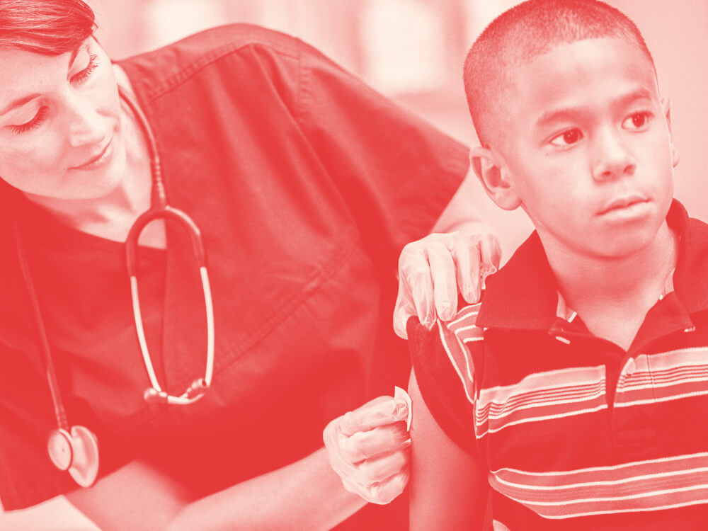 A pediatric nurse cleans a spot on a child's upper arm.
