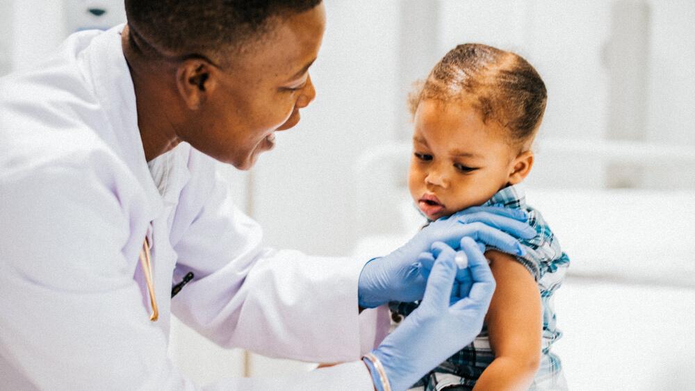 A pediatric nurse gives a child a shot in the upper arm.