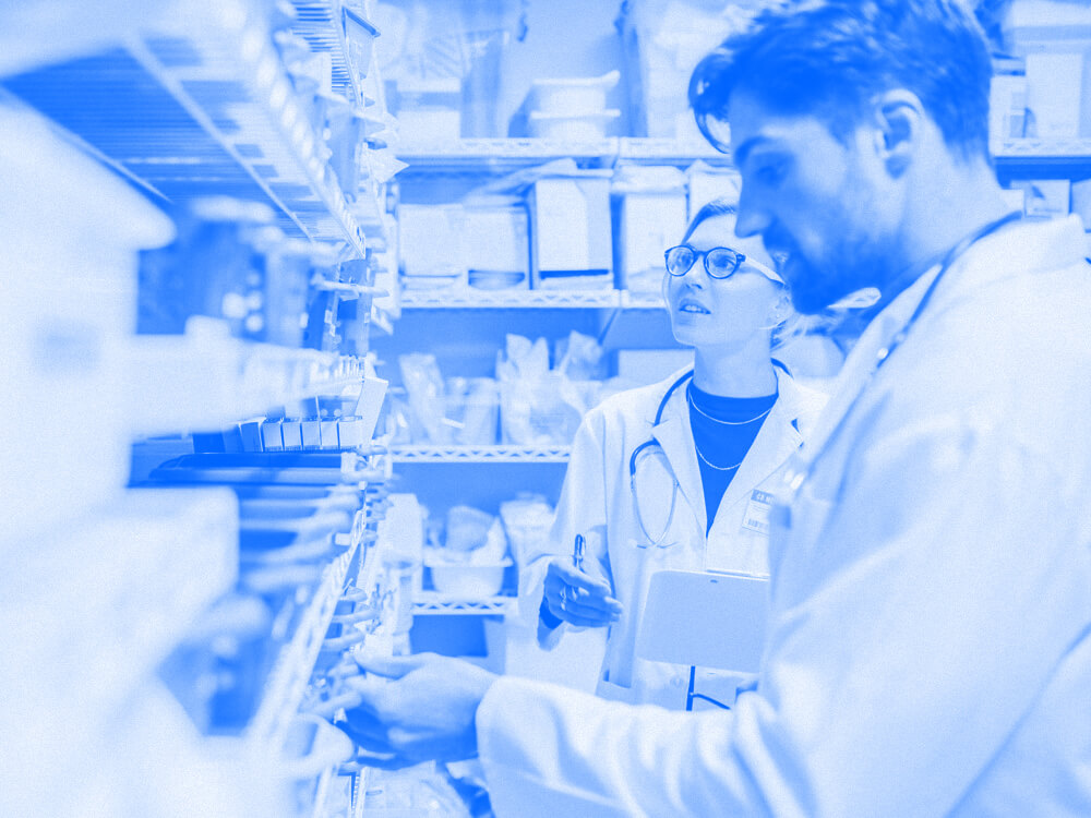 Two pharmacy technicians in front of shelves of medications.