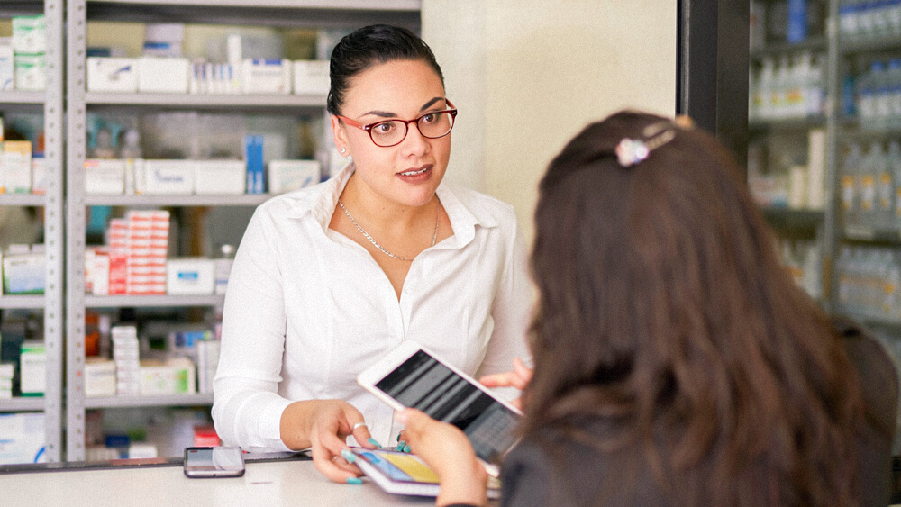 A pharmacy tech consults with a person picking up a prescription.