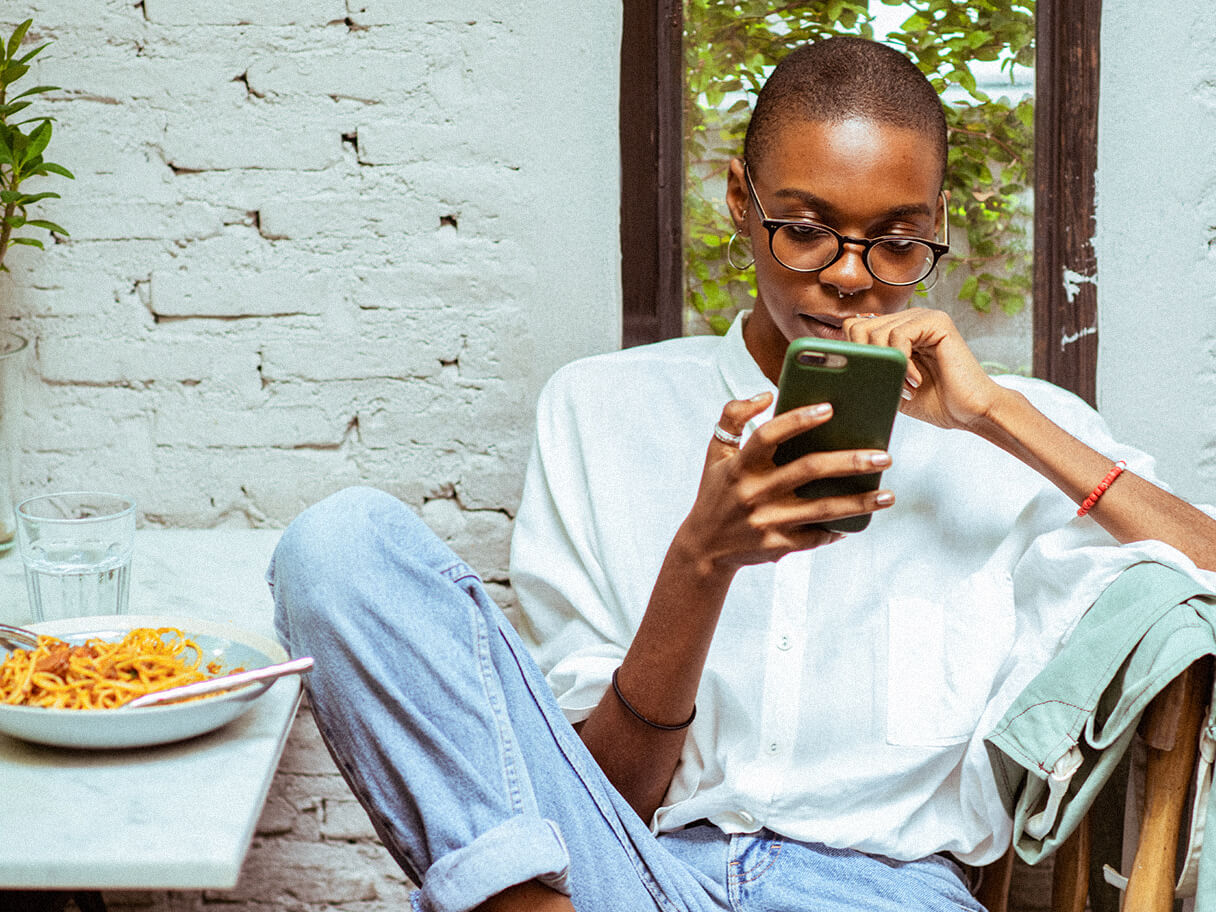 A student studies on their phone with their leg propped up against a dining table.