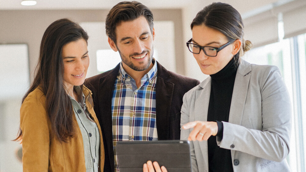 A realtor stands with a couple and holds a tablet for them to review together.