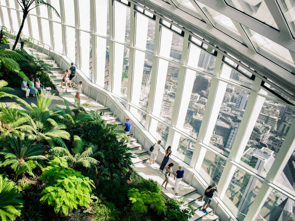 Inside of a building with a high glass ceiling, lots of green plants, and people walking along a walkway.