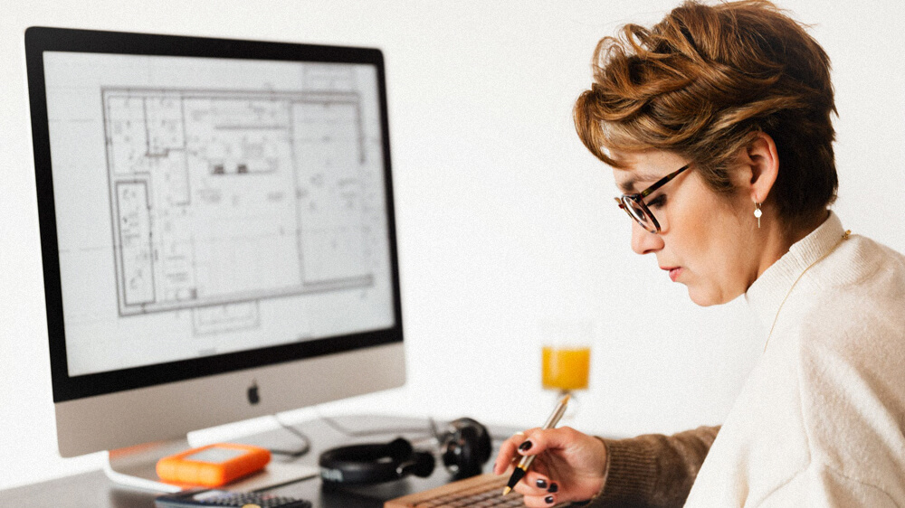 A person makes notes at their computer that shows a blueprint.