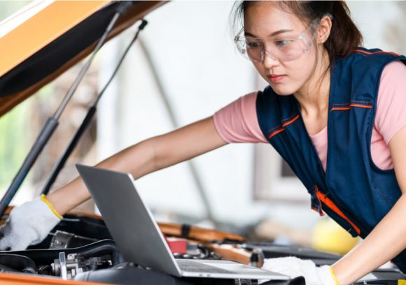 Automotive technician works on an engine while looking at a computer.