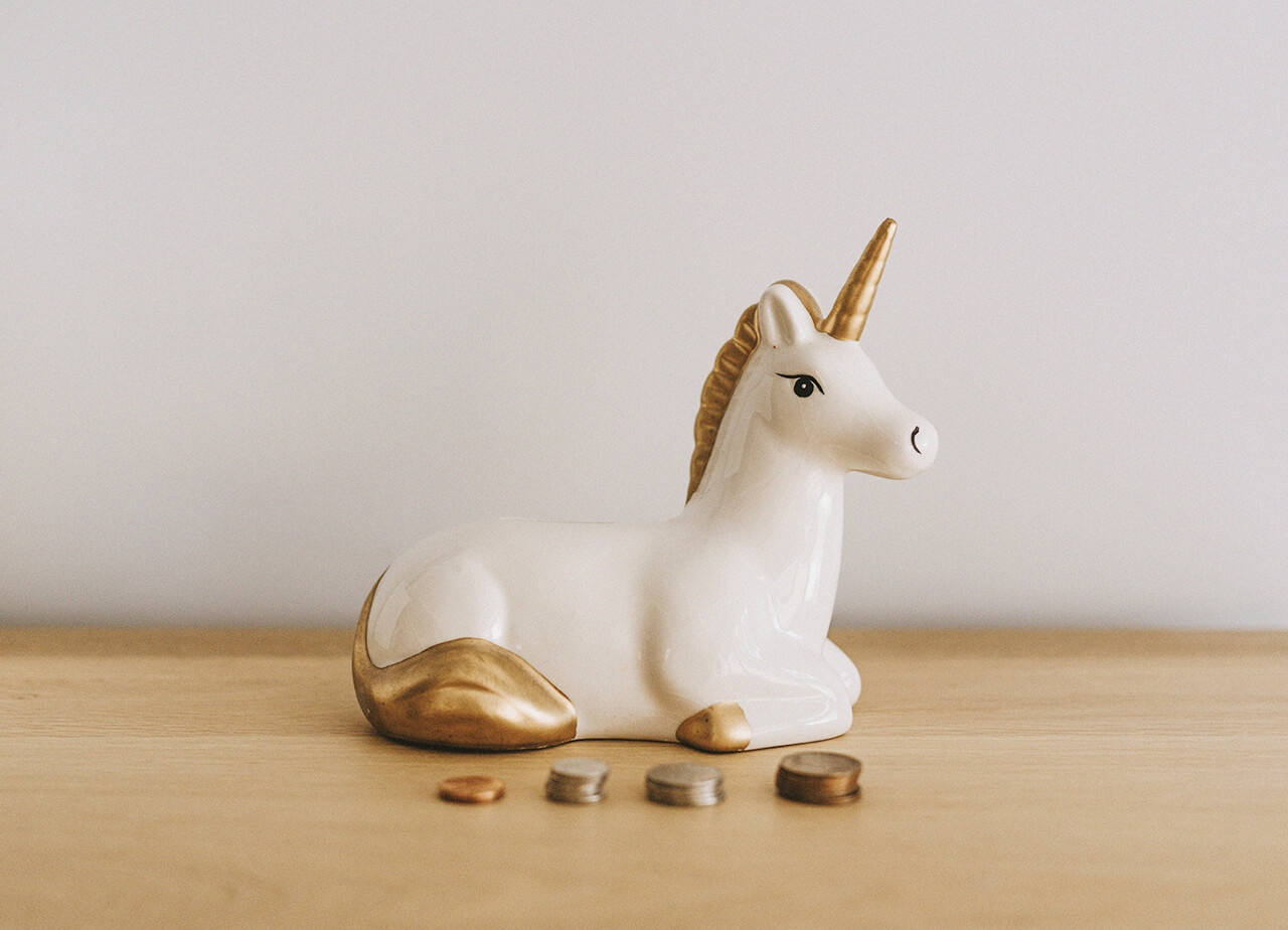 A white and gold ceramic unicorn on table in front of piles of coins.