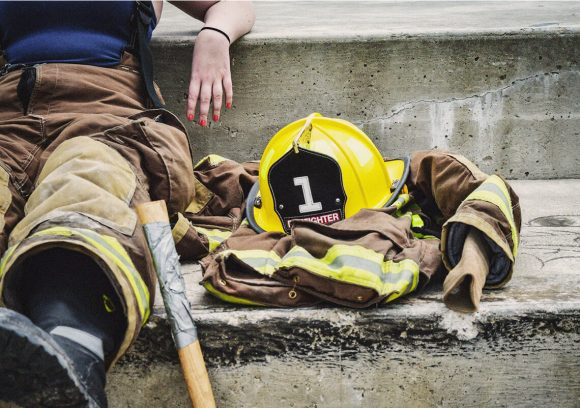 Firefighter seated on concrete steps next to their helmet and jacket. Close-up.