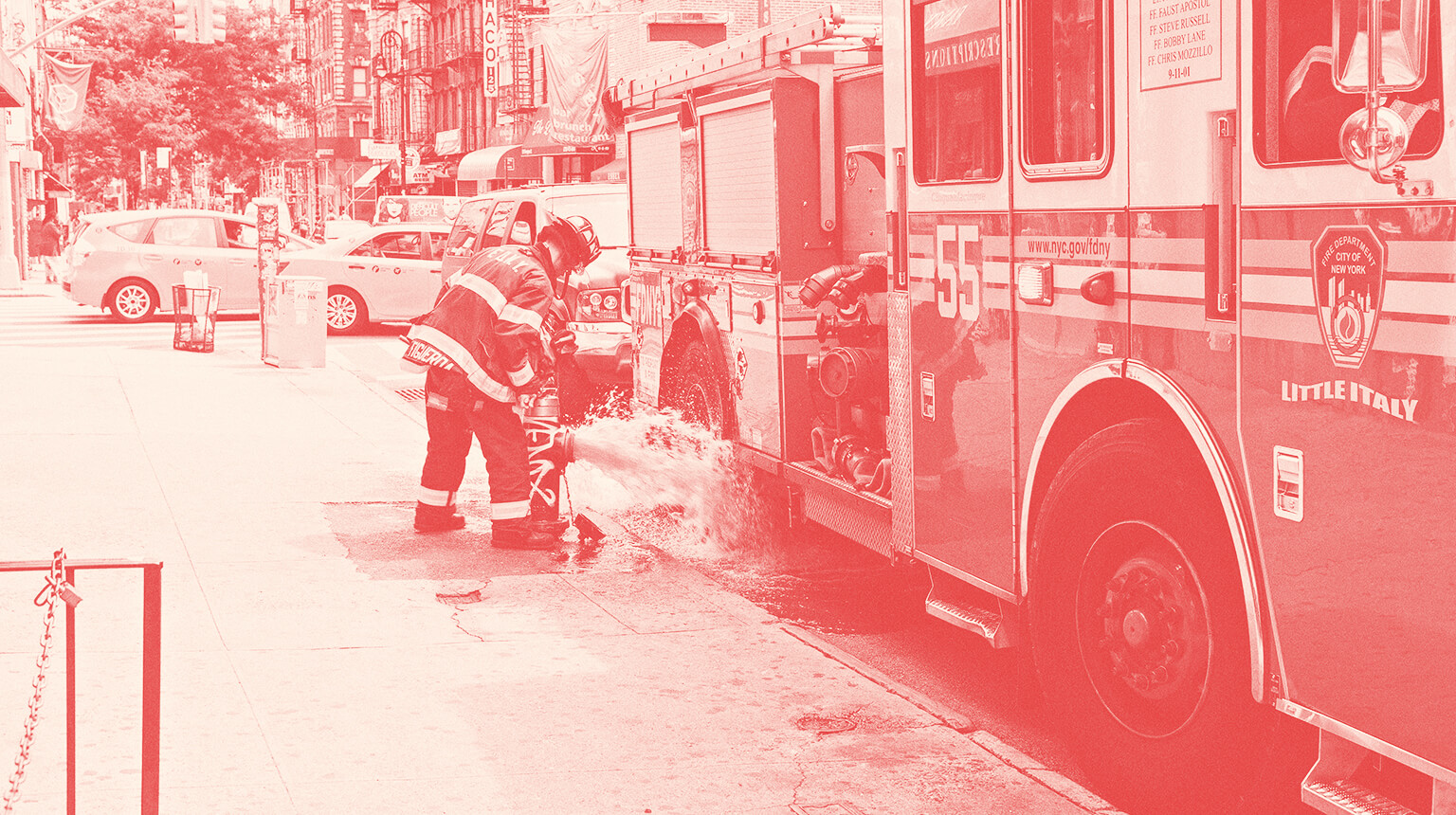 Firefighter standing next to a firetruck while monitoring an open fire hydrant.