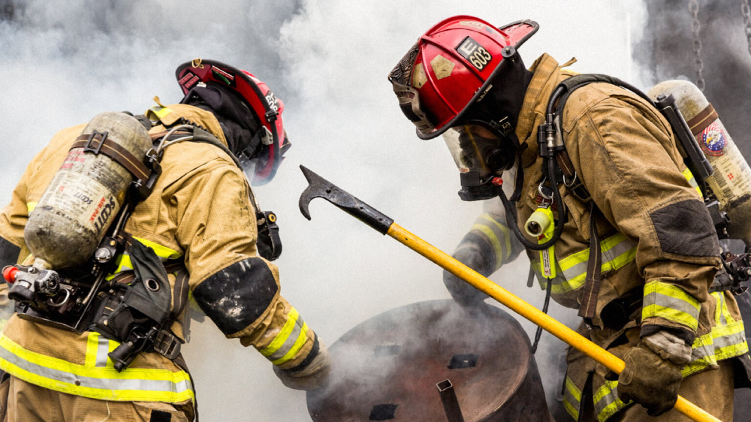 Two firefighters in full gear working to move a barrel while holding a hook.