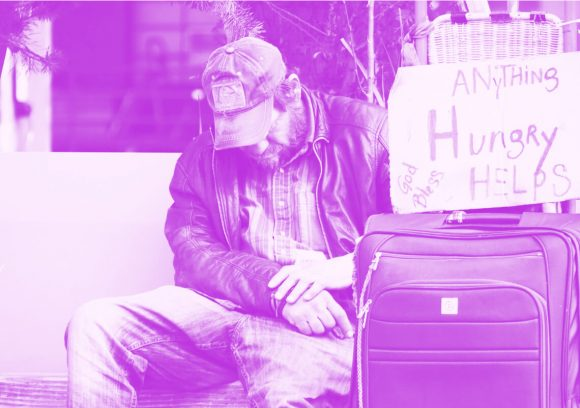 Homeless person sitting next a suitcase and sign asking for help.