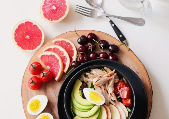 Top-down view of a healthy salad featuring avocado, grapefruit, cherries, and hard-boiled egg.