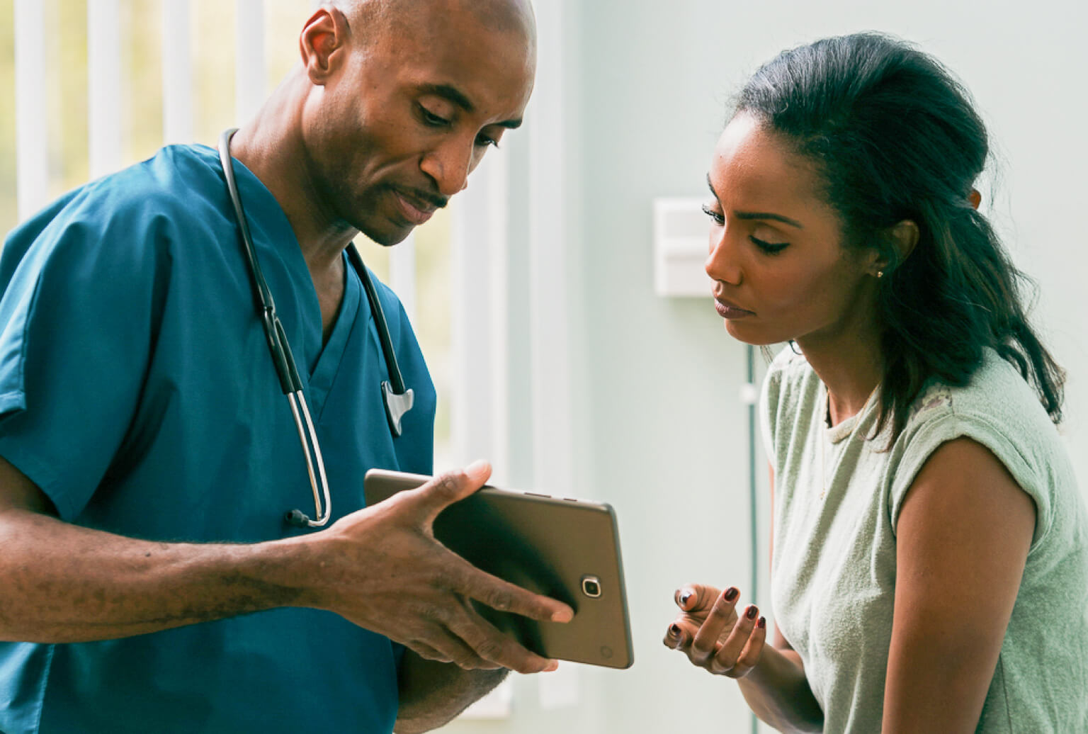A CNA wearing a stethoscope shows a patient information on a tablet.
