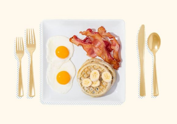 Bacon, eggs, waffles, and cut bananas on a square plate with silverware on either side.