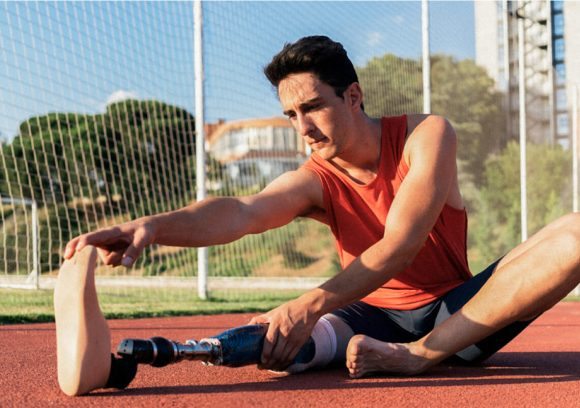 Person with prosthetic leg sitting on an outdoor track stretching.