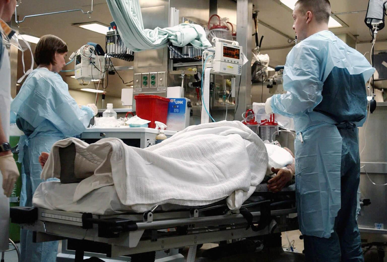 Two trauma nurses treat a patient lying on a gurney in a hospital.
