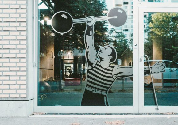 Exterior of gym with vintage window decal of person holding a retro weight.
