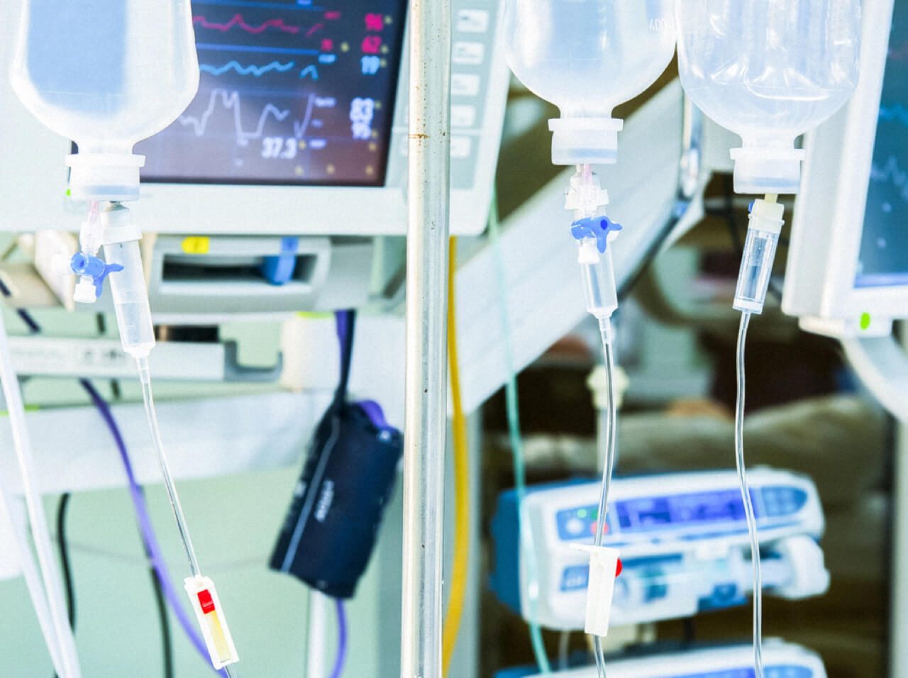 IV bags and heart rate monitor in a hospital setting. Close-up.