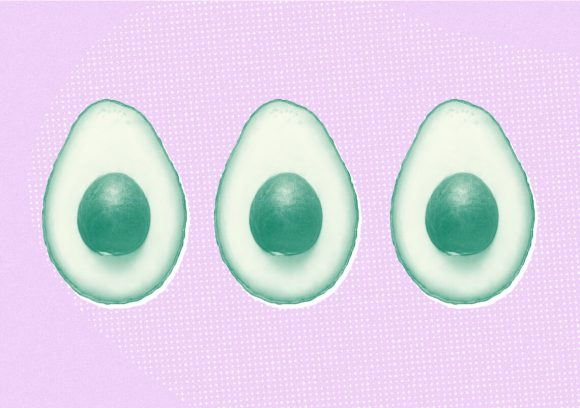 Row of three avocados cut in half on a pink background.