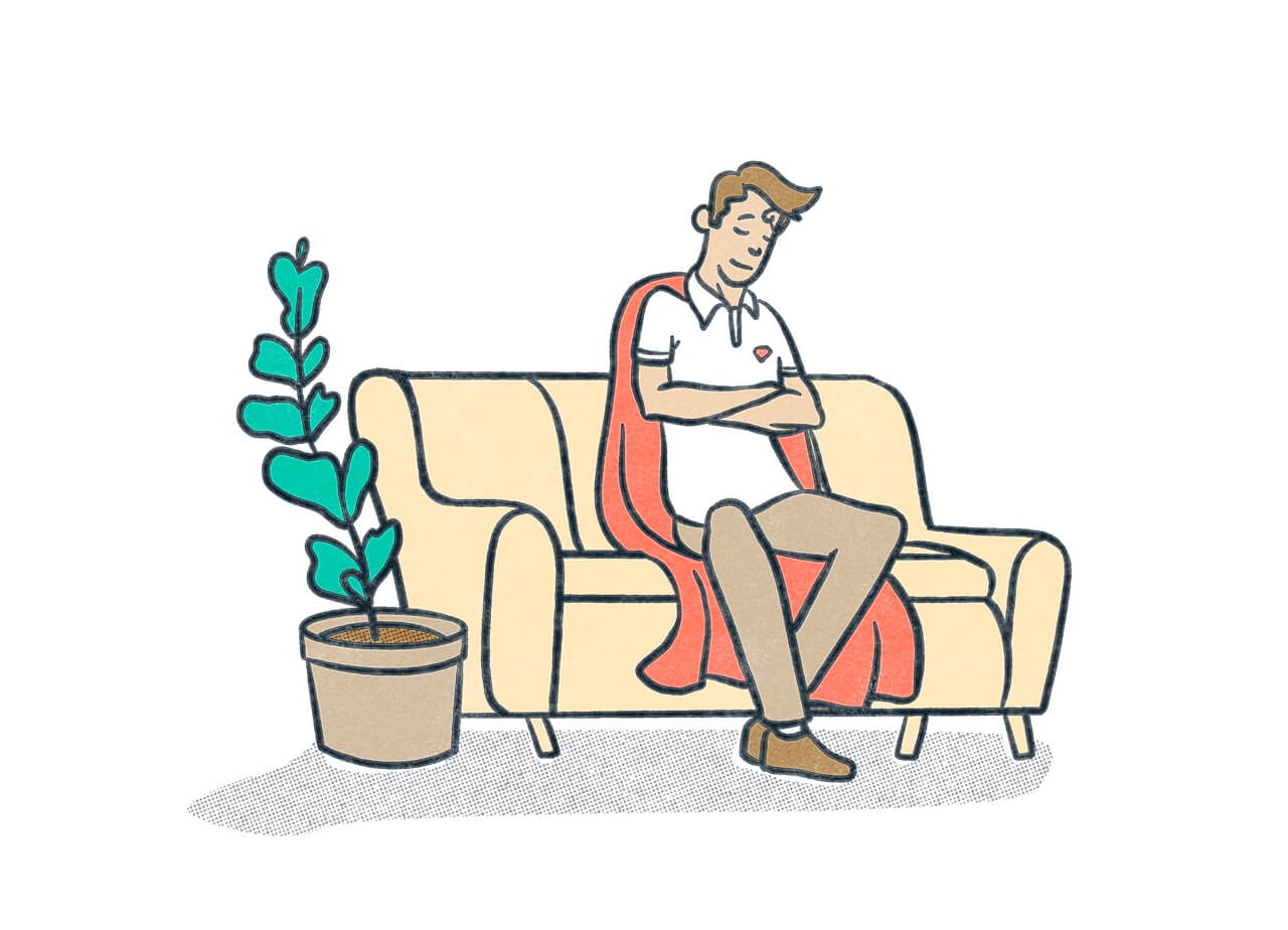 A person wearing a cape resting comfortably on a couch next to a plant.