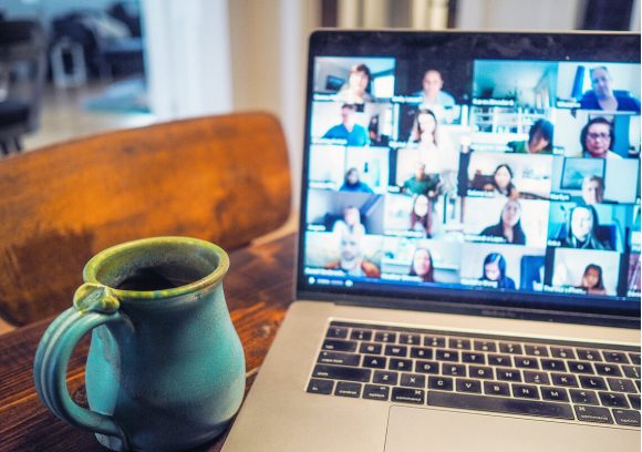 Coffee mug is sitting next to a computer showing a virtual meeting with multiple participants.