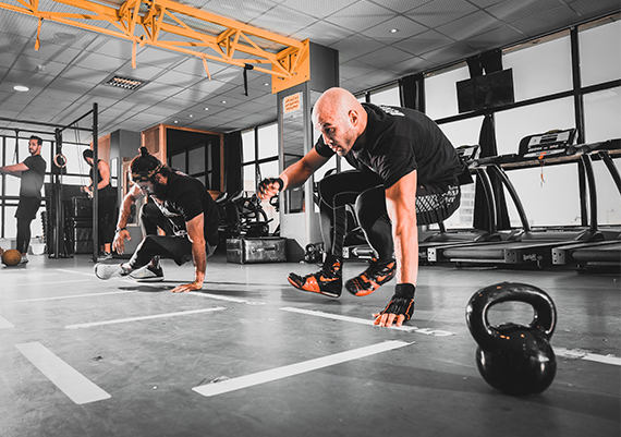 Two tactical personnel engaged in tactical training at a gym.