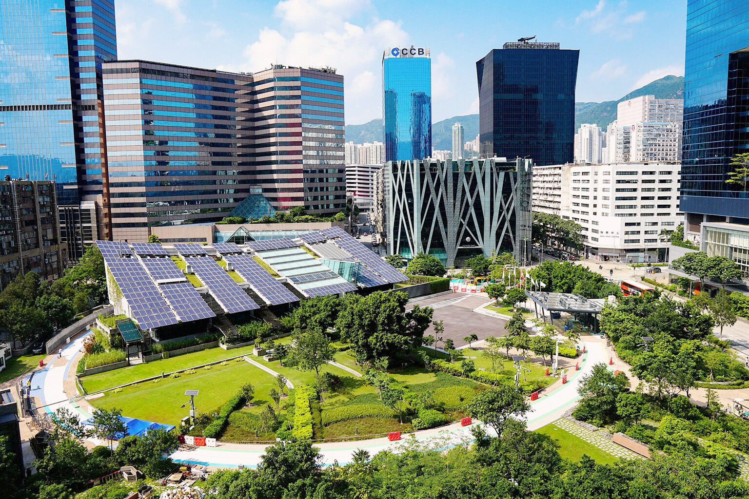 View of a city with tall buildings and large amounts of green space and solar panels.