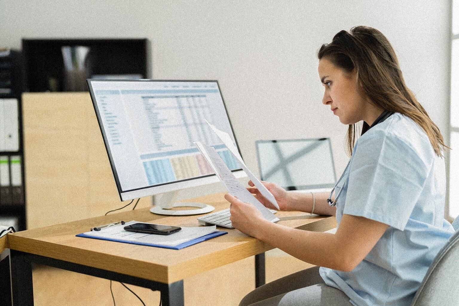 A certified medical coder sits a desk in front of a computer comparing paperwork.