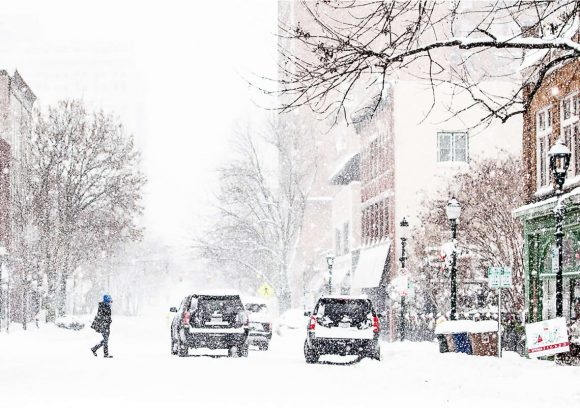 Person walking across a city street covered in snow during winter.