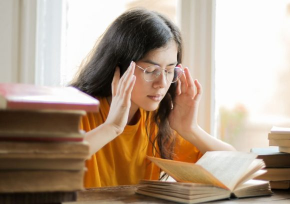 Person feeling stressed out while sitting a table full of books.