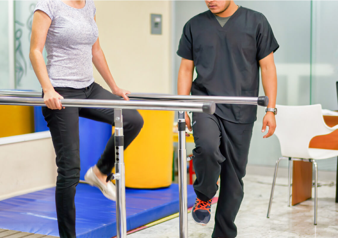 Occupational Therapist helping a patient on parallel rehabilitation bars.