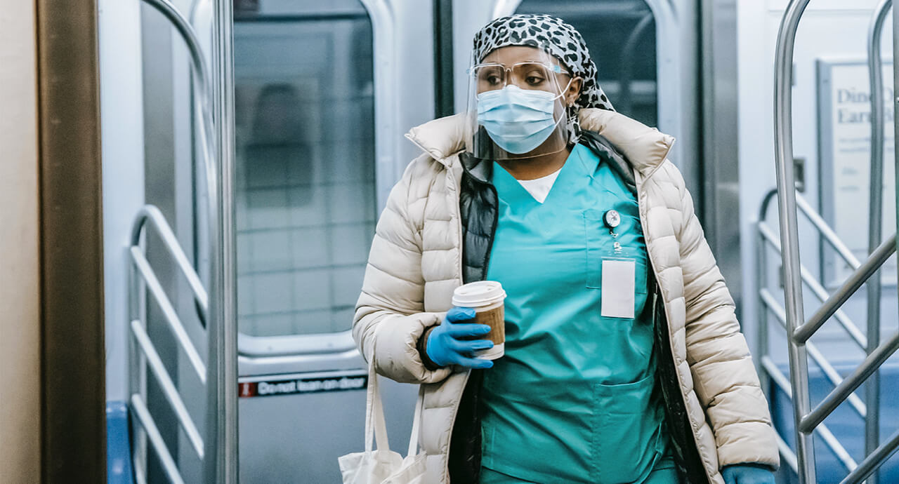 A nurse wearing a face shield and mask holding and holding a cup of coffee enters into a subway car.