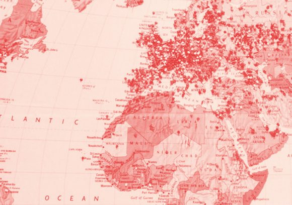 A map of Europe and Africa with lots of pushpins in various locations. Red-toned close up.