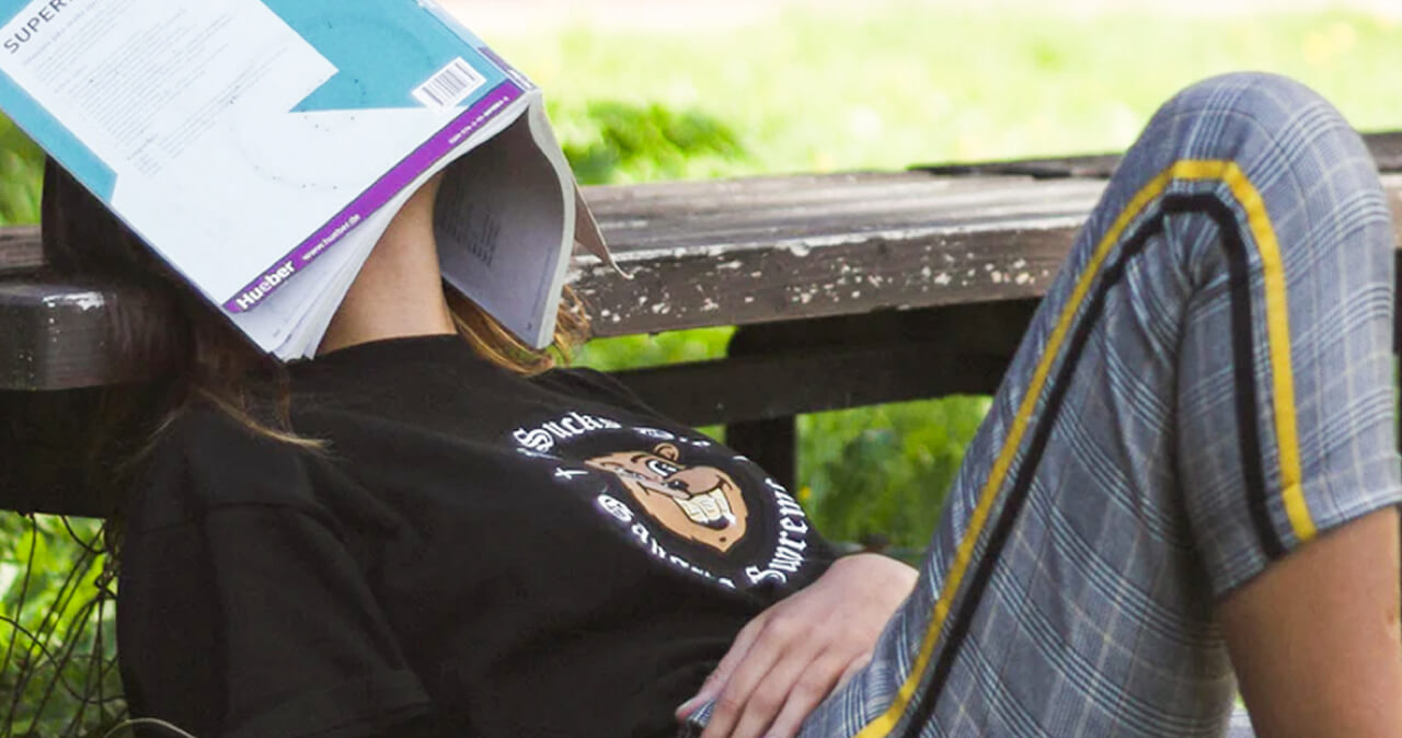 Person sitting on the ground, leaning back onto a park bench with a text book over their face.