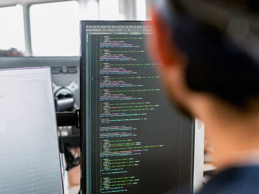 Over-the-shoulder view of a CompTIA Cloud+ professional looking at code on a computer screen.
