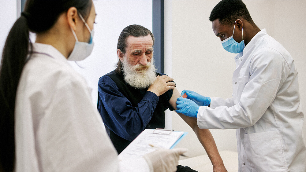Certified clinical medical assistant putting a bandage on a patient while a doctor holding a clipboard looks on.
