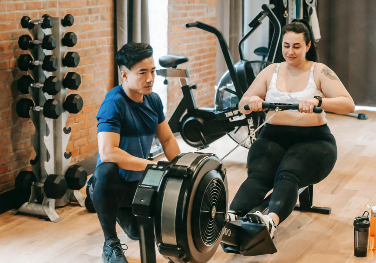 A person trainer works with a client on a rowing machine.