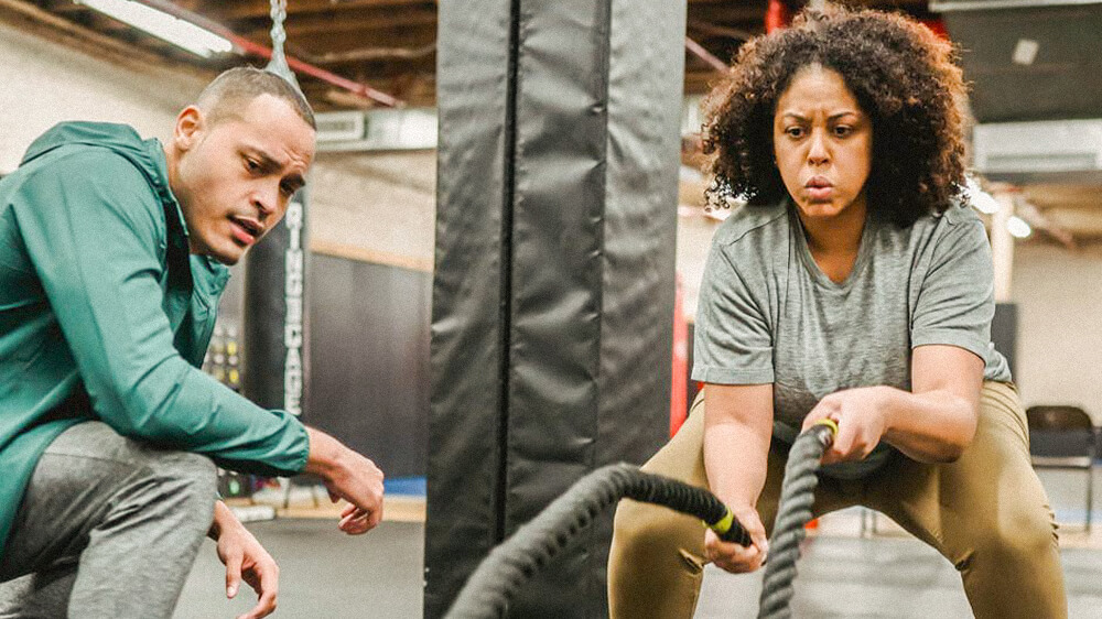 Certified personal trainer working with a client who is using battle ropes.