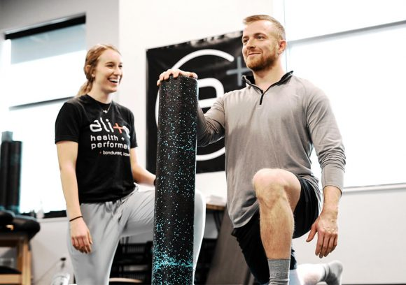 Personal trainer working with a client while using a foam roller.