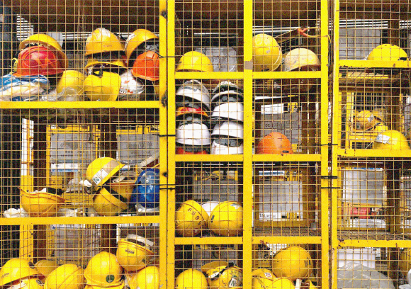 Multiple yellow hard hats stacked in a wire shelving unit.