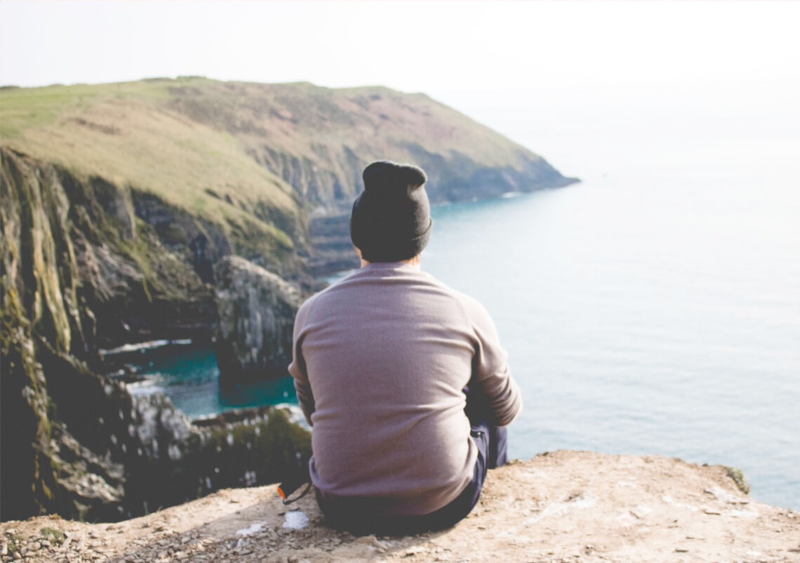 A person sitting on top of a hill looking out at the sea.