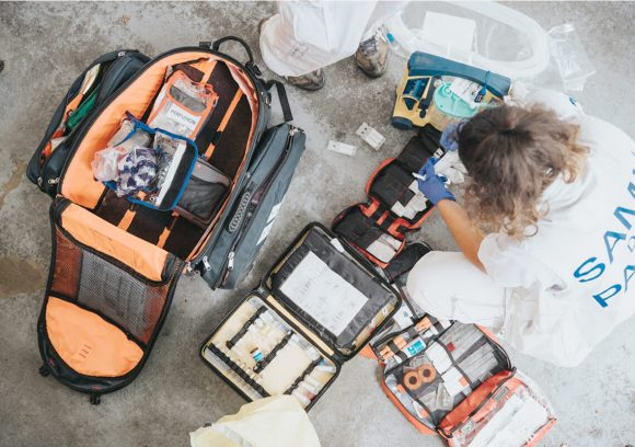 Emergency Medical Responder going through a medical kit. Overhead view.