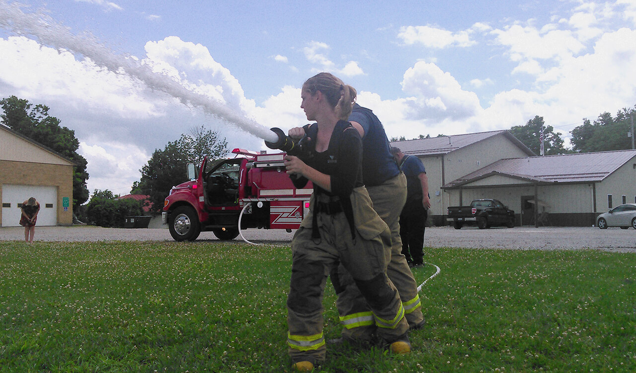 Lakota holding a fire hose during firefighter training.