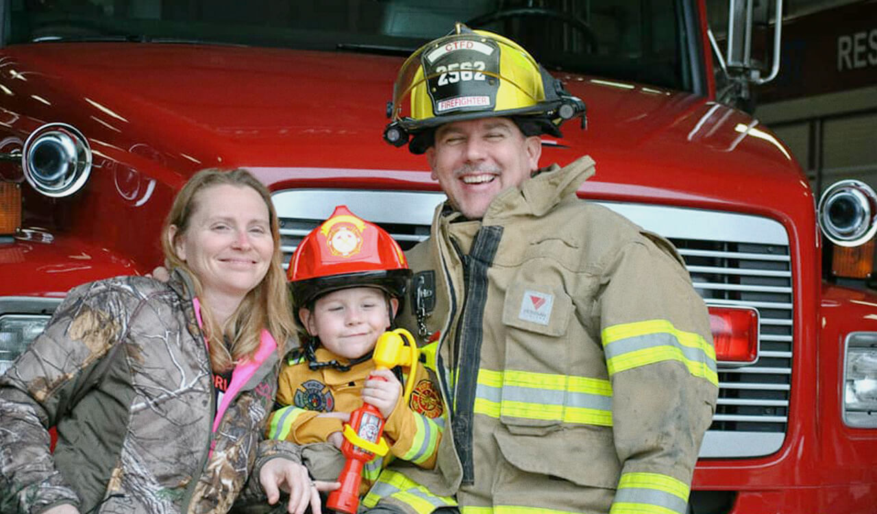 Todd May in a firefighter uniform with his family.