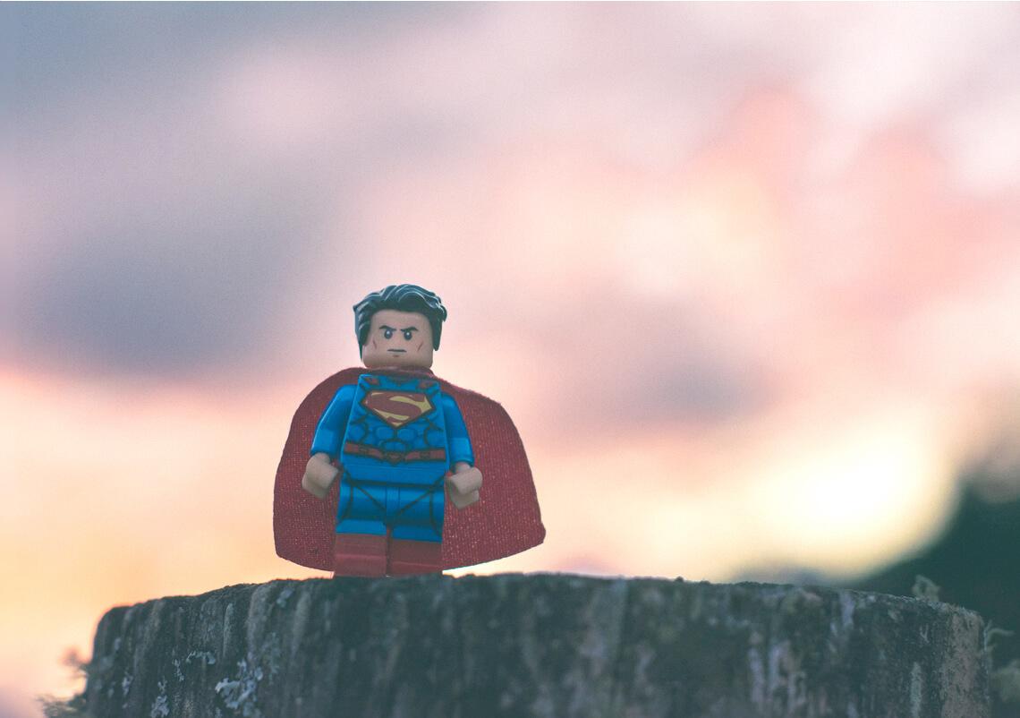 Miniature Superman figurine silhouetted against a sunset.