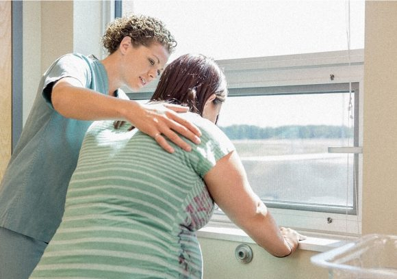 A midwife stands next to a patient at a window and helps her breath during labor contractions.