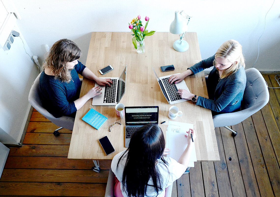 Three project managers sitting a table together while working on computers.