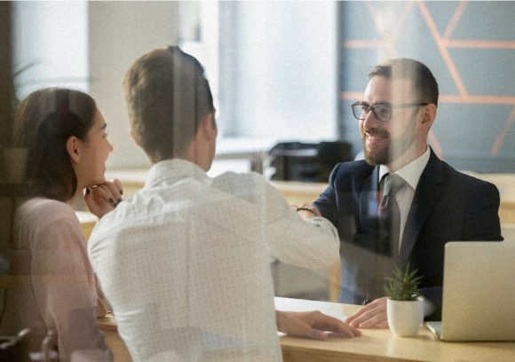 Two people meet with a certified financial planner at an office. One person is shaking the CFP's hand.