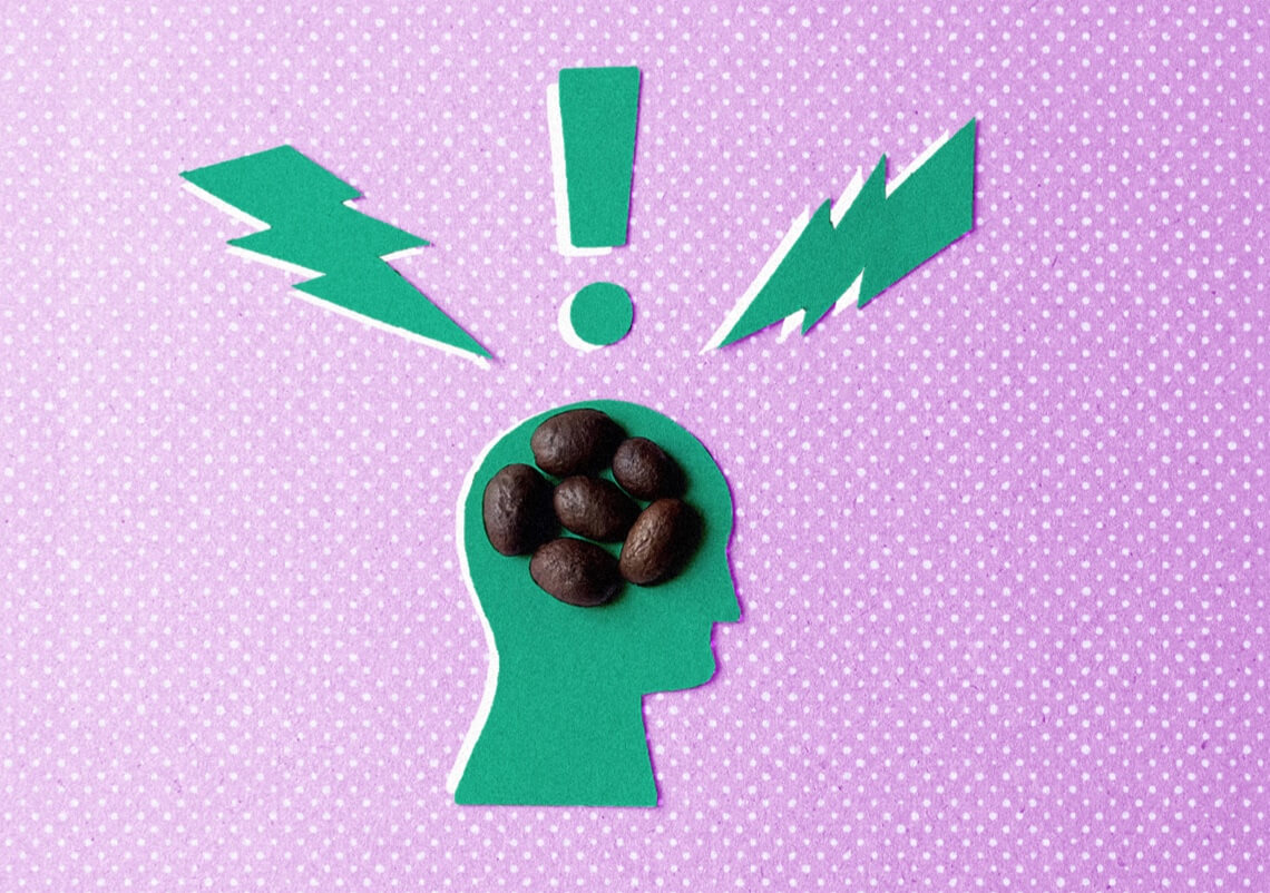 Paper cutout of a head with coffee beans on top of it and lightening bolts coming out of the top on a pink background.