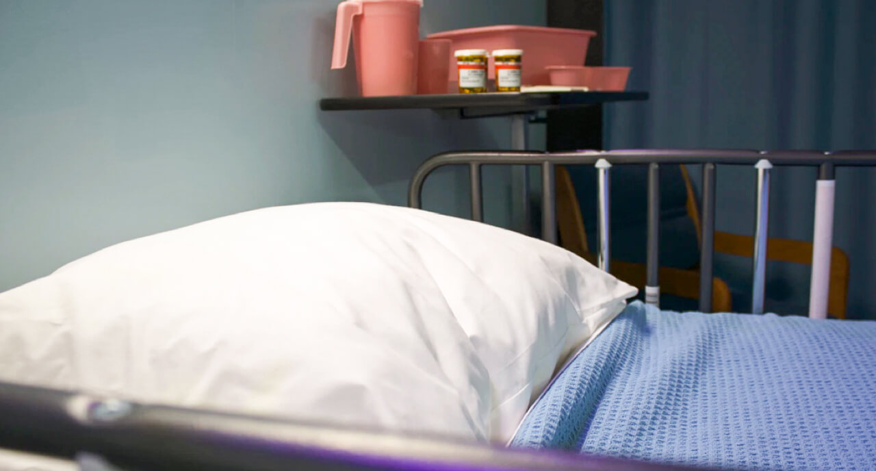 A hospital bed in front of a side table with medications and pink plastic containers.