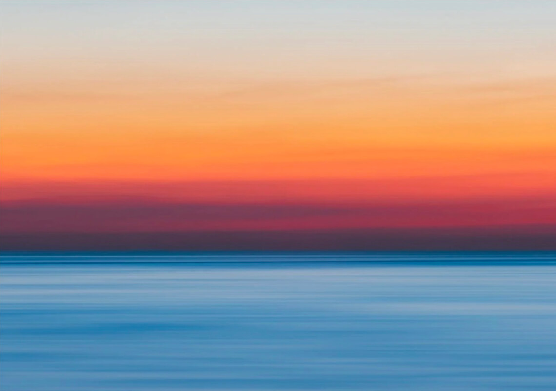 An orange sunset over a body of blue water.
